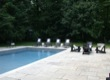 The reverse view of the classic swimming pool with loungers