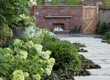 An angle on the lush verge surrounding the brick fireplace