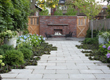 This rectangular backyard is given life by a mix of stone, brick and greenery