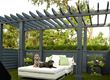 Two dogs lounge under a blue pergola, resting on a white oversized ottoman