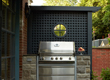 A built-in bbq surrounded by stone and gorgeous blue latticework