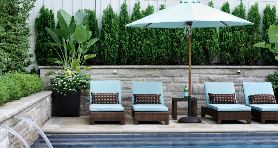 Photo slideshow of Artistic Gardens' design projects: squared photo of loungers with patio umbrella arranged on flagstone terrace by swimming pool